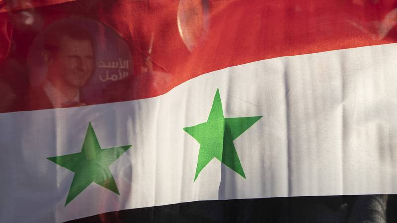In this May 23, 2021, file photo, the Syria national flag is displayed at a gathering at...