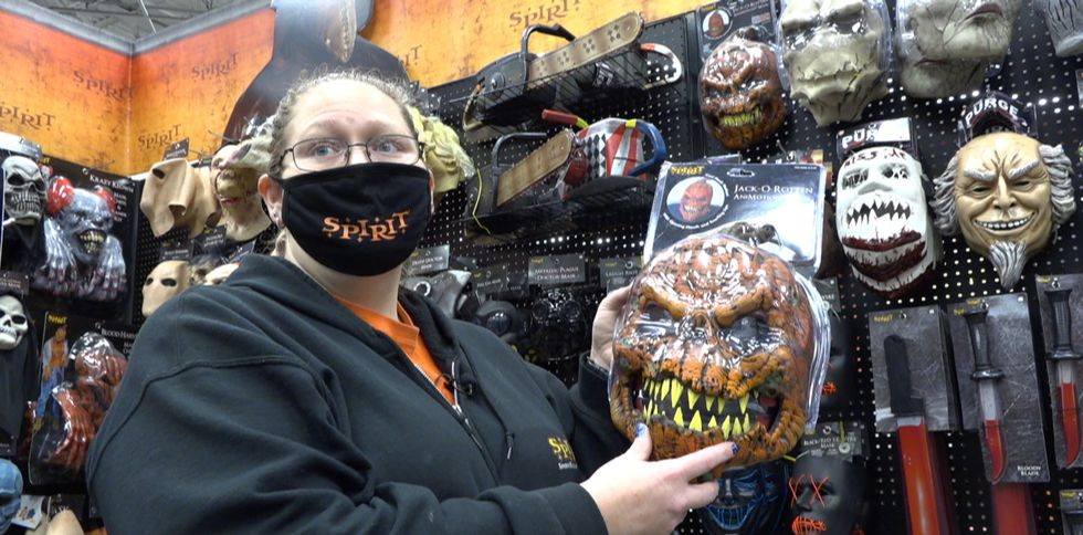 Spirit Halloween store manager, Whitney Turner showing off a best-selling animotion mask.