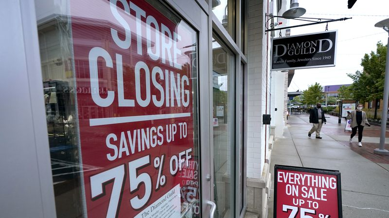 Passers-by walk past a business storefront with store closing and sale signs, Wednesday, Sept....