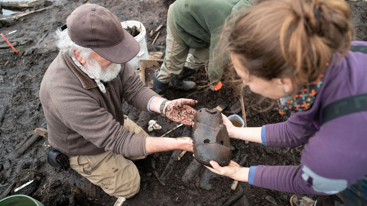 Dr. Rick Knecht of the University of Aberdeen and the lead archaeologist on the Nunalleq project, hands a mask up to another archaeologist. (Photo courtesy of Alice Watterson)