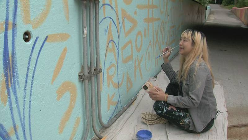 Artist Rejoy Armamento works on a mural under the C Street bridge on the Chester Creek Trail.