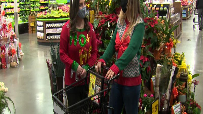 Ellie Baty and Kristen Durand go shopping for food to put in their pantry packs before donating...
