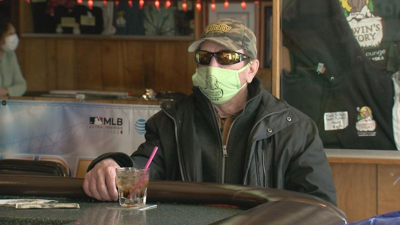 A masked patron enjoys a drink inside Darwin's Theory on Monday, March 8, as restrictions on...