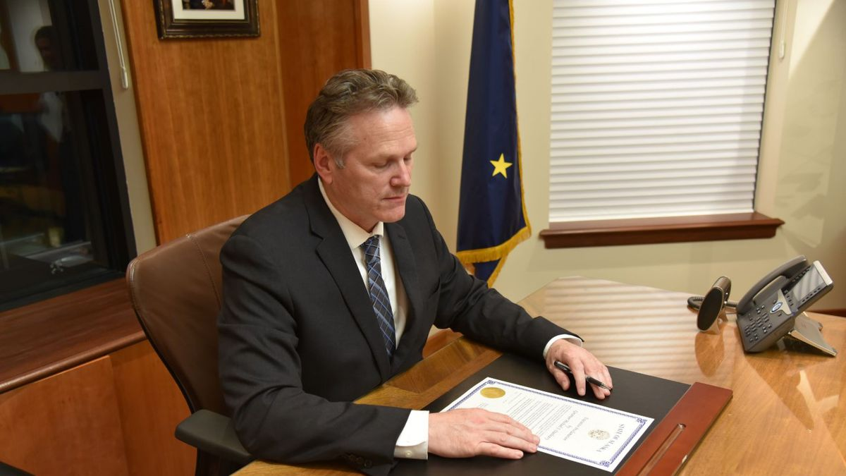 Gov. Mike Dunleavy signing the formal proclamation calling the Legislature into a special session Wednesday evening.