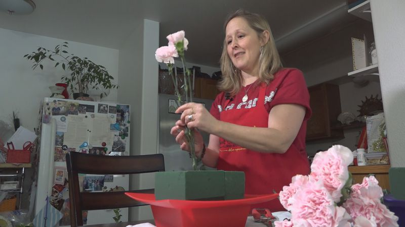 Red Carpet Flower Boutique owner operator, Billie Saunders prepares the materials for one of...