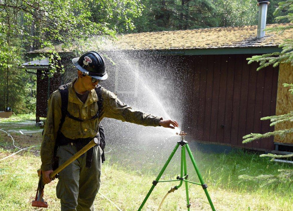 Yukon Fire Crew member Antonio Sisco checks a sprinkler as his crew tests structure protection...