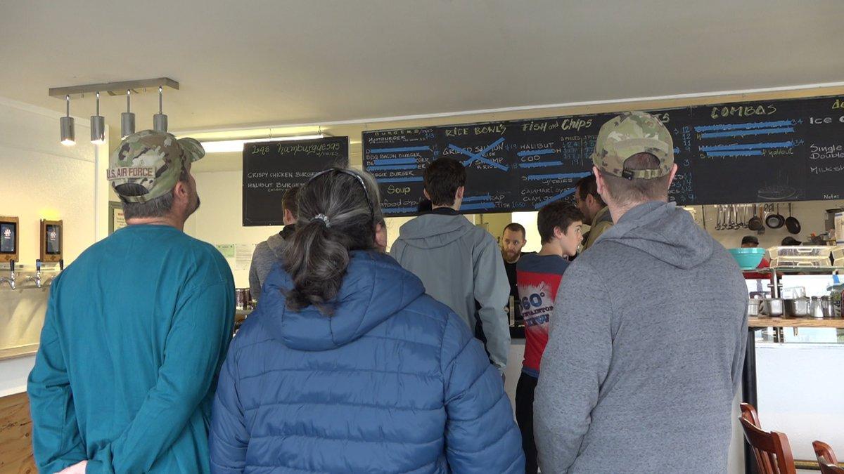 A long line at Alaska Seafood Grill in Seward, Alaska. On the menu board, many items were...