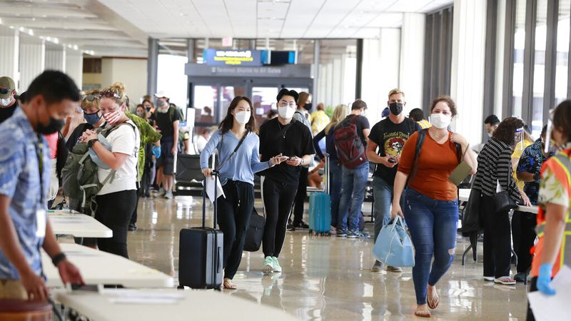 Visitors arrive at the airport Thursday, Oct. 15, 2020, in Honolulu. A new pre-travel testing...