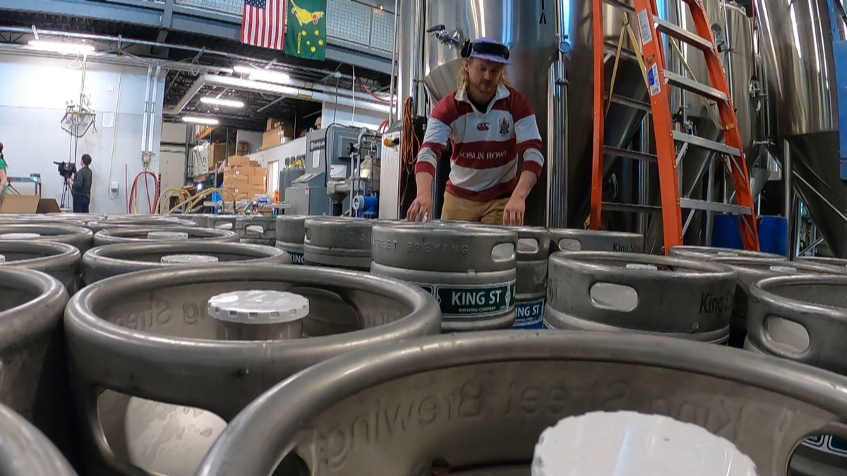 Workers at King Street Brewing filling up the kegs to be sold to bars and brewpubs. They didn't...