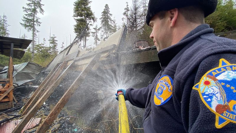 An Alaska State Trooper works to put out a hot spot at a residential fire in Port Protection on...