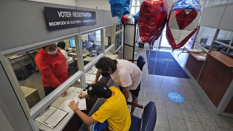 Lucas Saez, foreground, 22, fills out his voter registration form as his father Ramiro Saez,...