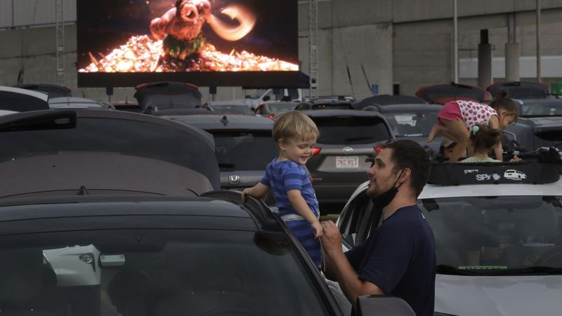 Kevin Rokos, right, and his 1-year-old son Merritt, both of Boston, attend a drive-in movie...