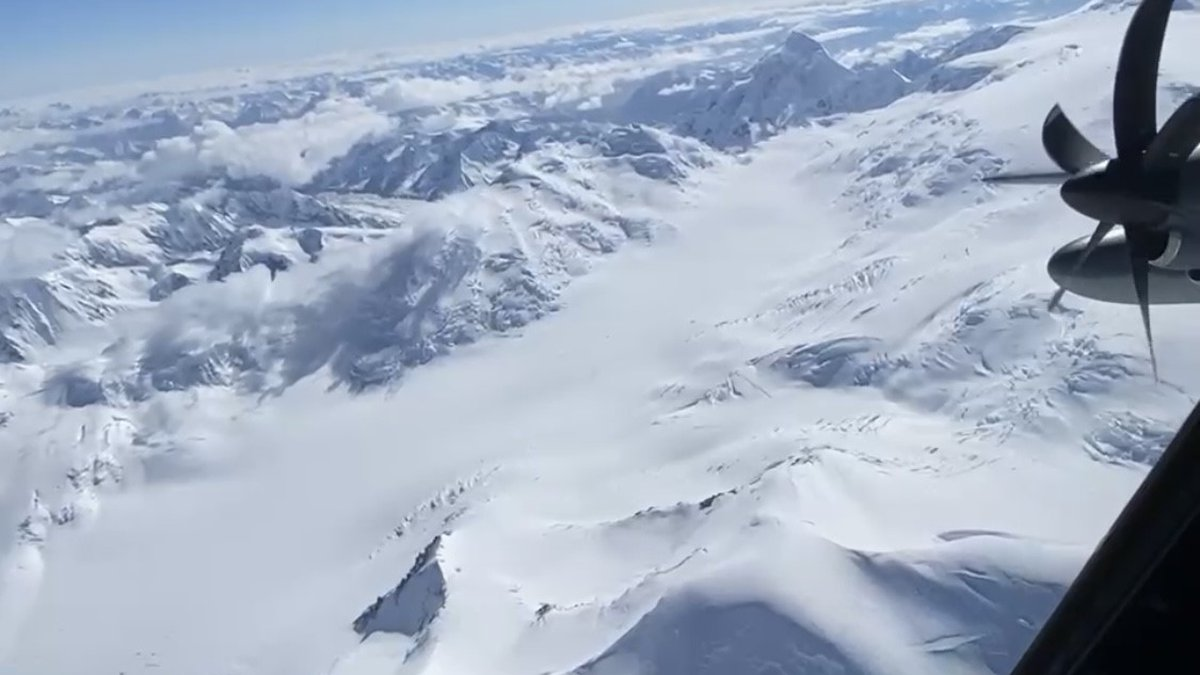 An Alaska Air National Guard HC-130 hovers over the rescue site of 12 stranded mountaineers in...