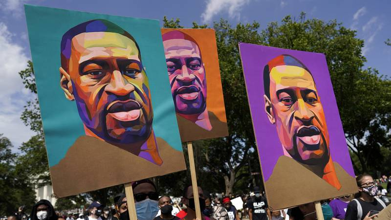In this Aug. 28, 2020, file photo, people carry posters with George Floyd on them as they march...