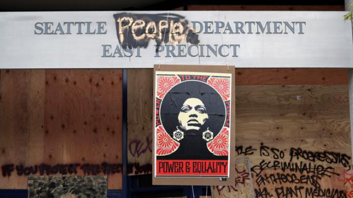 A 1970's-era poster of activist Angela Davis hangs at a boarded up and closed Seattle police...