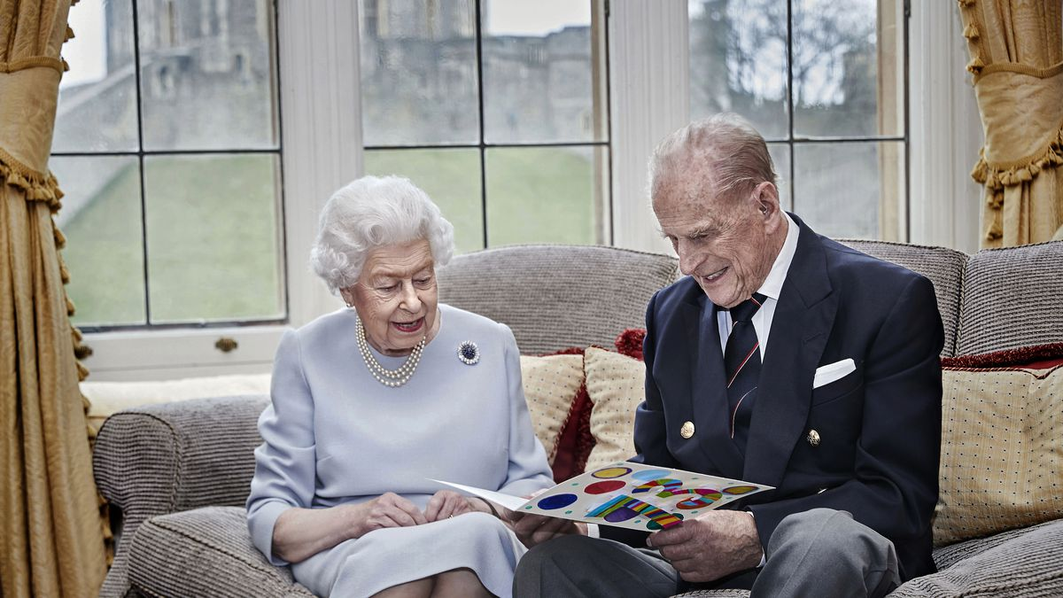 Britain's Queen Elizabeth II and Prince Philip, Duke of Edinburgh look at a homemade wedding...