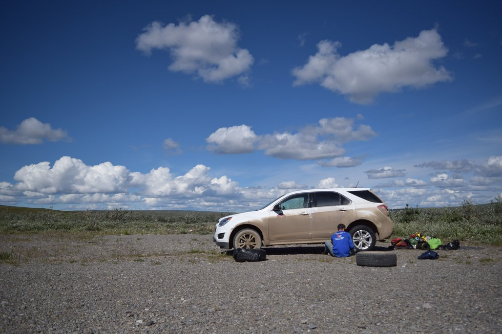 Sean Maguire changes a tire at a campground off the Dalton Highway. June 2020 photo by Beth...