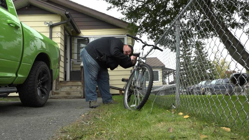 """Nick Stewart in Spenard resetting his """"bait bike"""" he set up to deter thefts after a couple got..."""