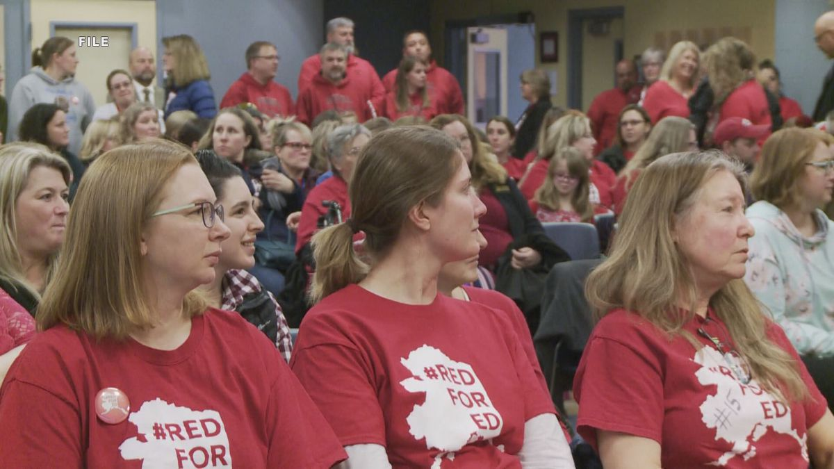 Teachers sit in unity during a school board meeting. Mat-Su teachers have worked under old...