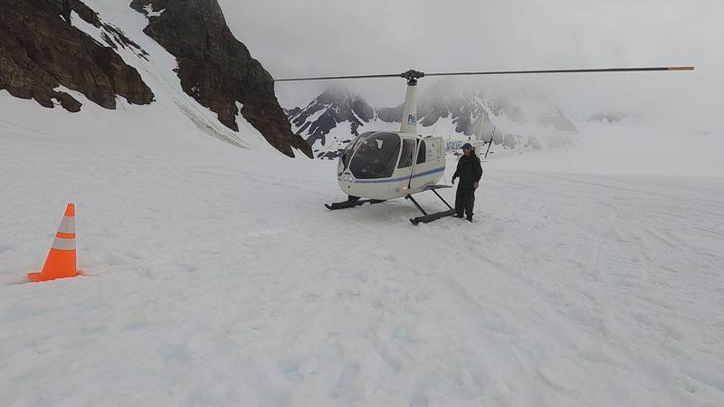 A helicopter lands on Godwin Glacier for a glacier dog sledding tour with Turning Heads Kennel.