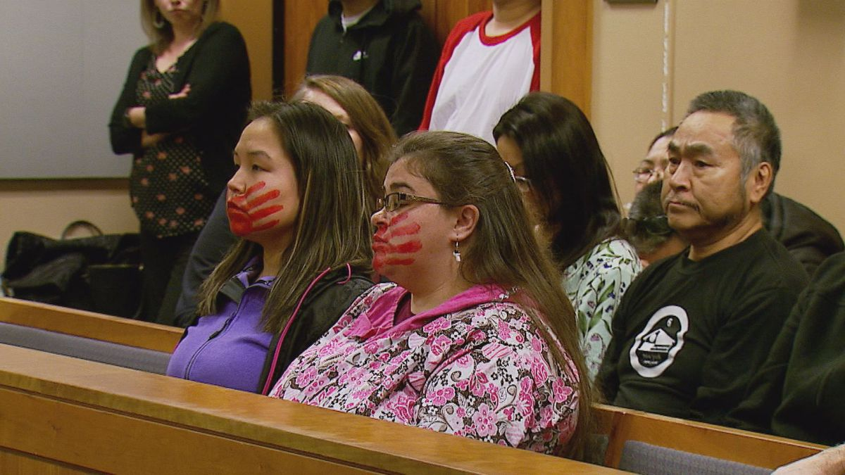 Joanne Sakar and Natasha Gamache, supporters of Veronica Abouchuk sit at Brian Smith's arraignment wearing red hands over their faces, symbols of a nationwide movement to improve the startling statistics about missing and murdered indigenous women.
