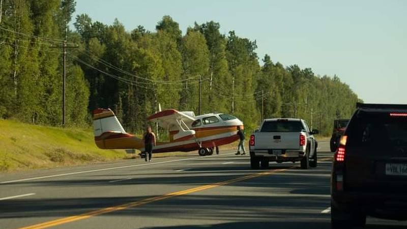 People help push the single-engine Seabee plane off of Parks Highway near Talkeetna on Sunday.