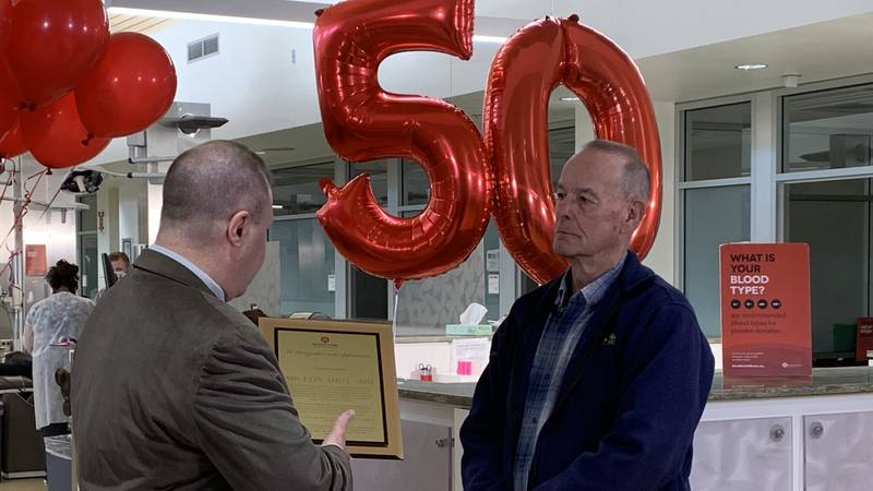 Ed Lamm accepts a plaque from Blood Bank CEO Bob Scanlon recognizing 50 years of giving blood.
