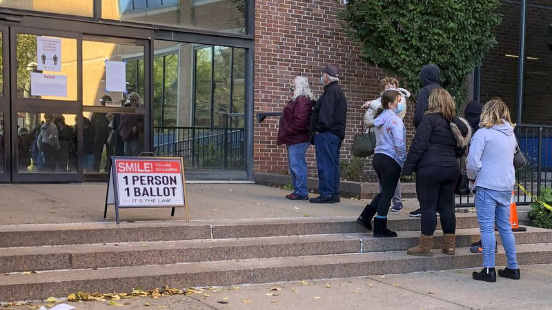 Voters wait in line outside the Bucks county government building in Doylestown, Pa., a suburb...