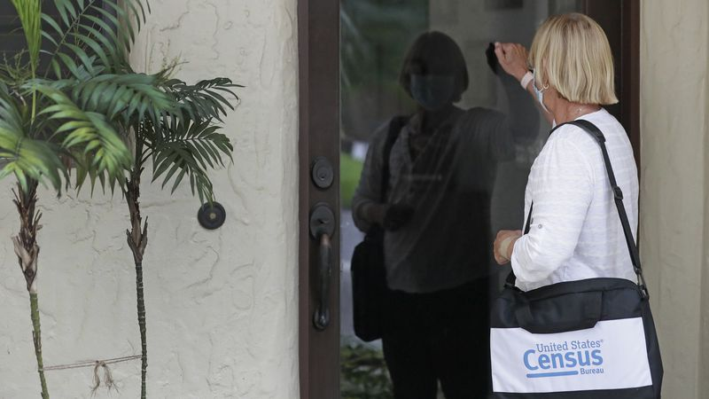 A census taker knocks on the door of a residence on Tuesday, Aug. 11, 2020, in Winter Park, Fla.