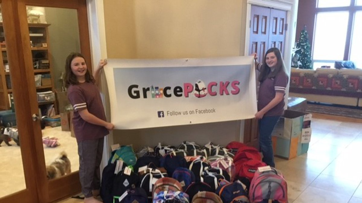 Emma and Abianne Kirschner stand with their GracePacks sign with the packs they are donating to...