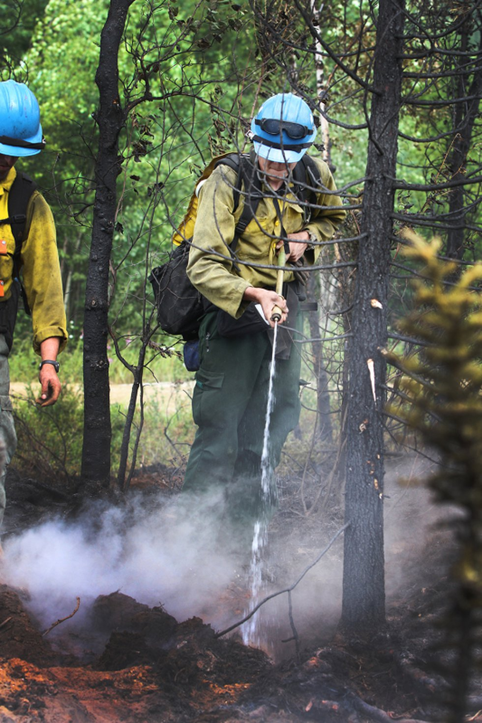 A member of the UAF Nanook Crew uses a Fedco to apply water to a hot spot while mopping up...