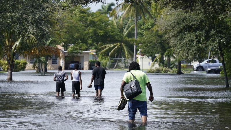 Residents walk a flooded street to reach their homes, Monday, Nov. 9, 2020 in Fort Lauderdale,...
