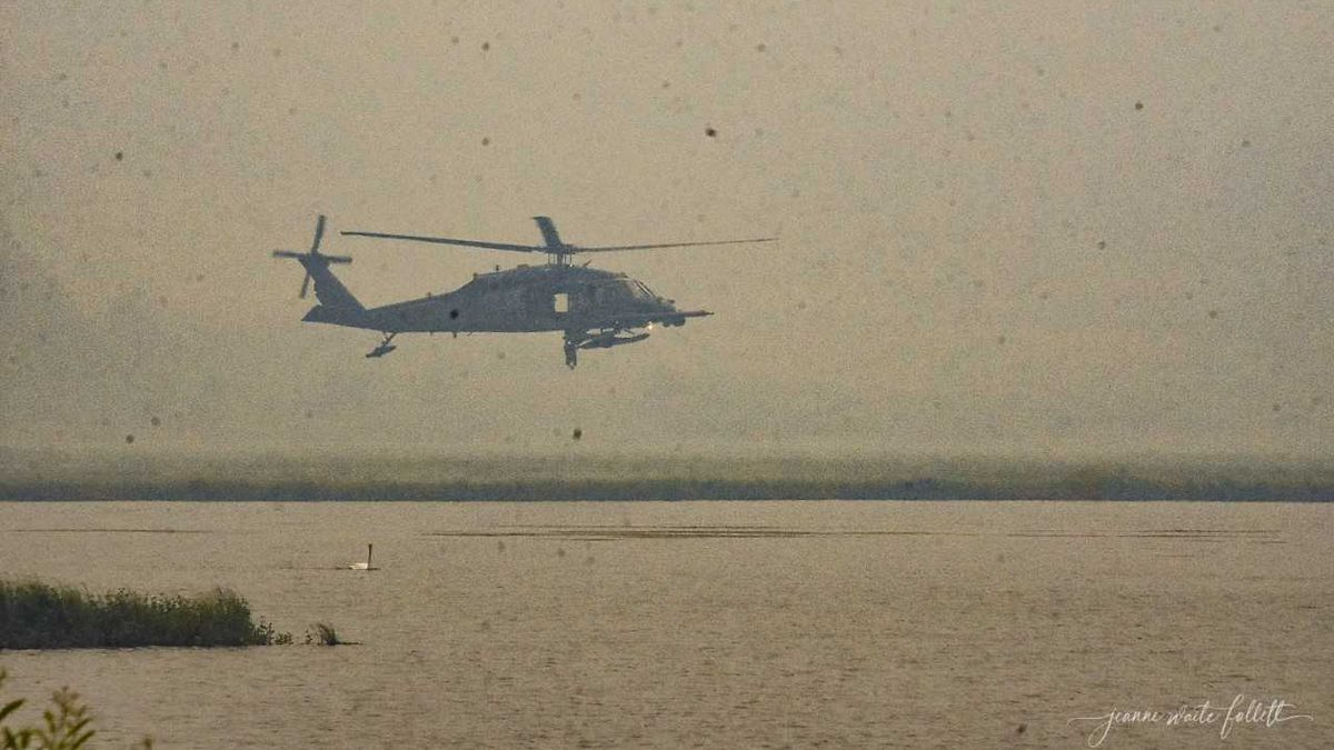 Air National Guard hovering in thick smoke over Tern Lake after putting two medics on the site of a small plane crash on the mountain north of the lake.
