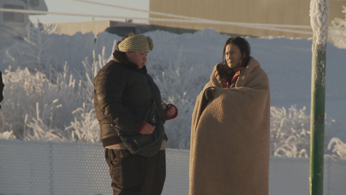 Two women stand outside Bean's Cafe, bundled against the cold. (KTUU)