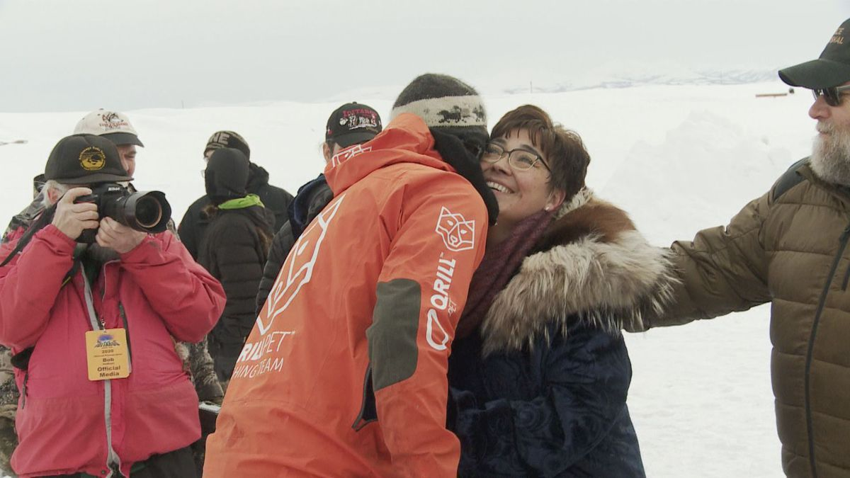 Middy Johnson's widow, Aurora Johnson, greets Thomas Waerner, the first musher to reach Unalakleet on Sunday.