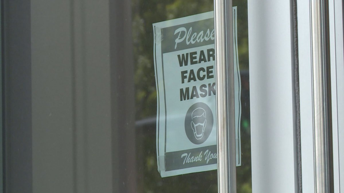 A sign asking patrons to wear a mask hangs on the window of a business.
