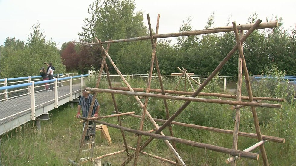 Artist Charlie Pardue constructs a traditional fish drying rack at Westchester Lagoon