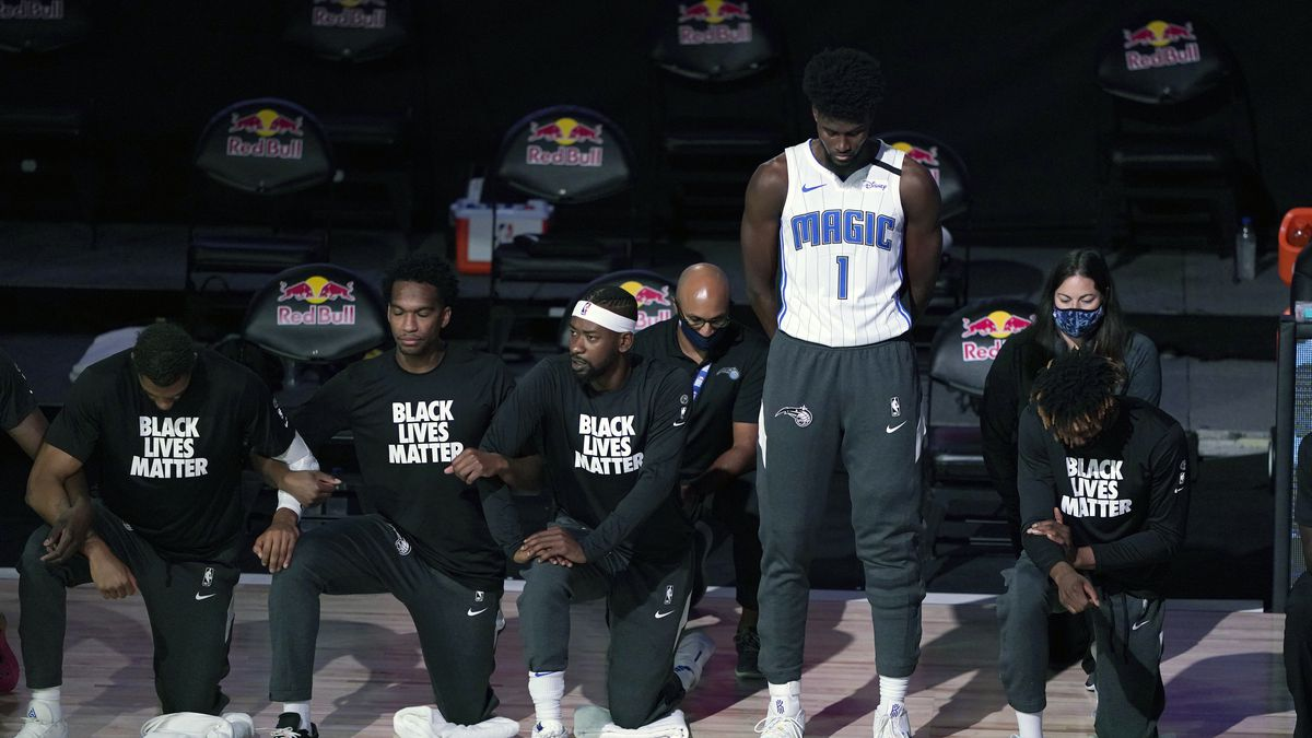 Orlando Magic's Jonathan Isaac (1) stands as others kneel before the start of an NBA basketball game between the Brooklyn Nets and the Orlando Magic Friday, July 31, 2020, in Lake Buena Vista, Fla.