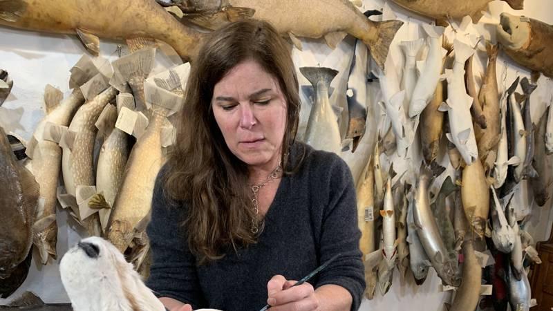 Longtime Alaska artist Romney Dodd paints an African animal mount with vivid designs.