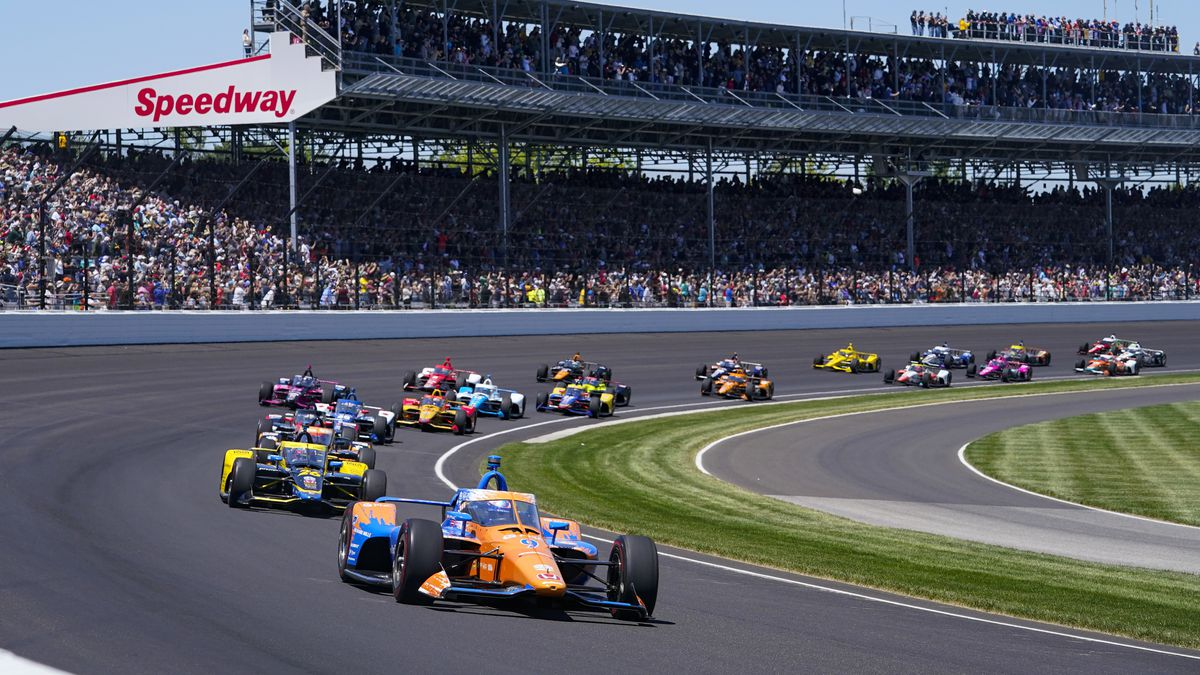 Scott Dixon of New Zealand leads the field through the first turn on the start of the...