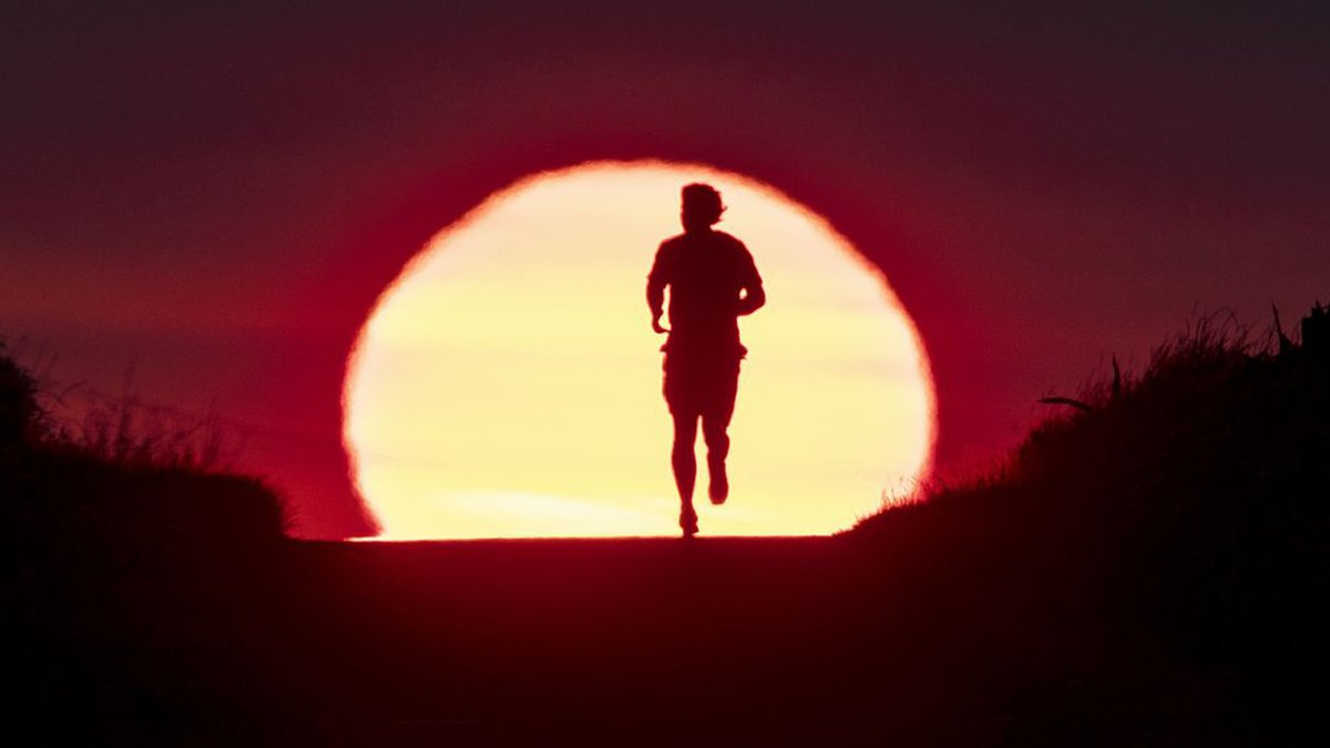 FILE - In this June 27, 2019 file photo a man runs on a small path as the sun rises in...