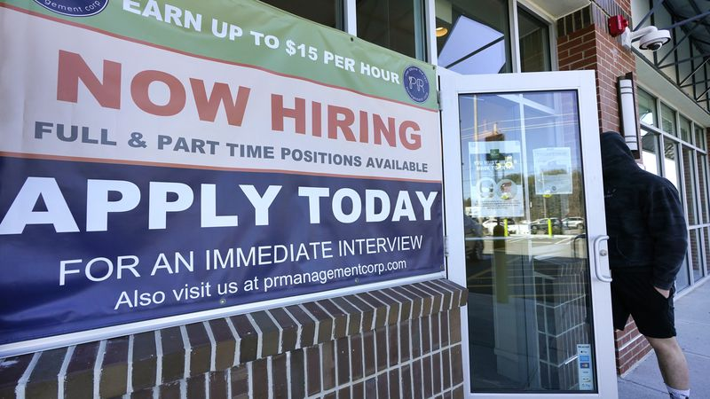 "A man walks into a restaurant displaying a ""Now Hiring"" sign, Thursday, March 4, 2021, in..."
