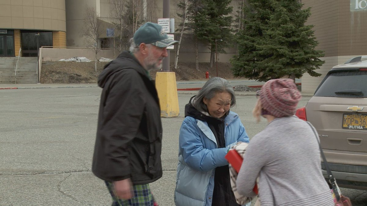 Roger Williams and Lucy Tall hug a caseworker from Beans Cafe who helped them find short-term...