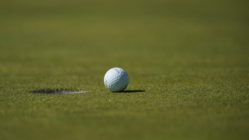 A detail view of a Titleist golf ball next to the hole on the practice green during the third...