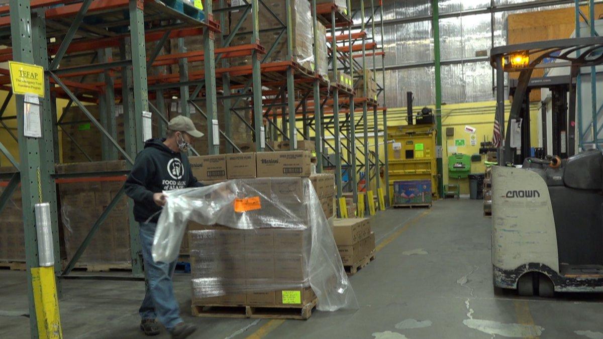 A volunteer at the Food Bank of Alaska restocking items