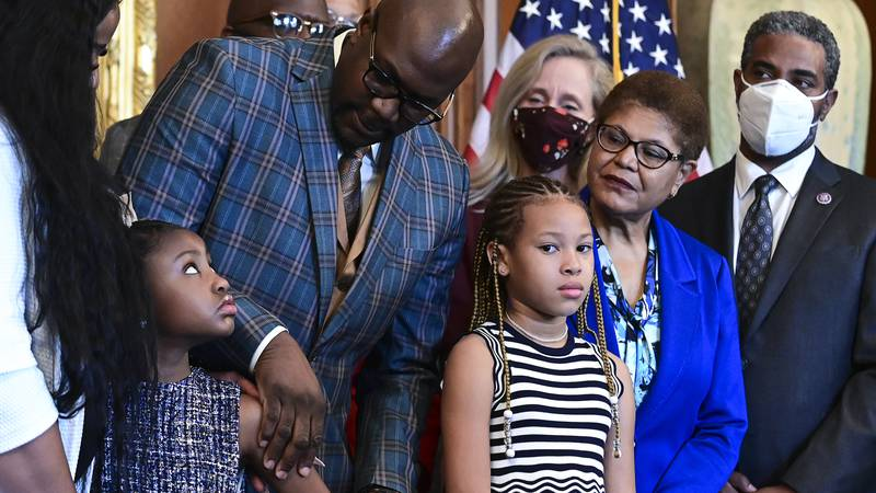 Philonise Floyd, George Floyd's brother, looks down at Gianna Floyd, George Floyd's daughter,...