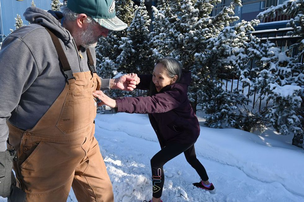 Roger Williams helps Lucy Tall step over a snow berm this week. The couple spent 10 years...
