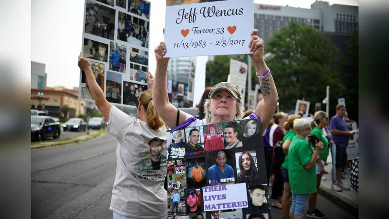 FILE - In this Aug. 17, 2018 file photo, Lynn Wencus of Wrentham, Mass., holds a sign with a...