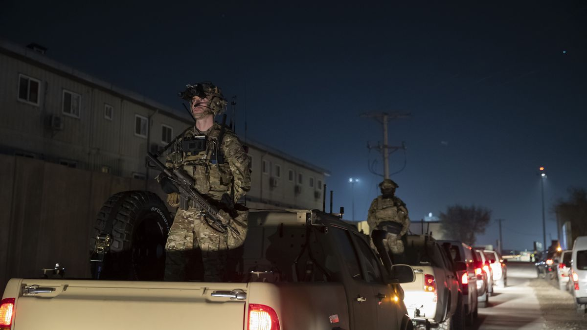 FILE - In this Nov. 28, 2019 file photo, armed soldiers stand guard in the motorcade for...