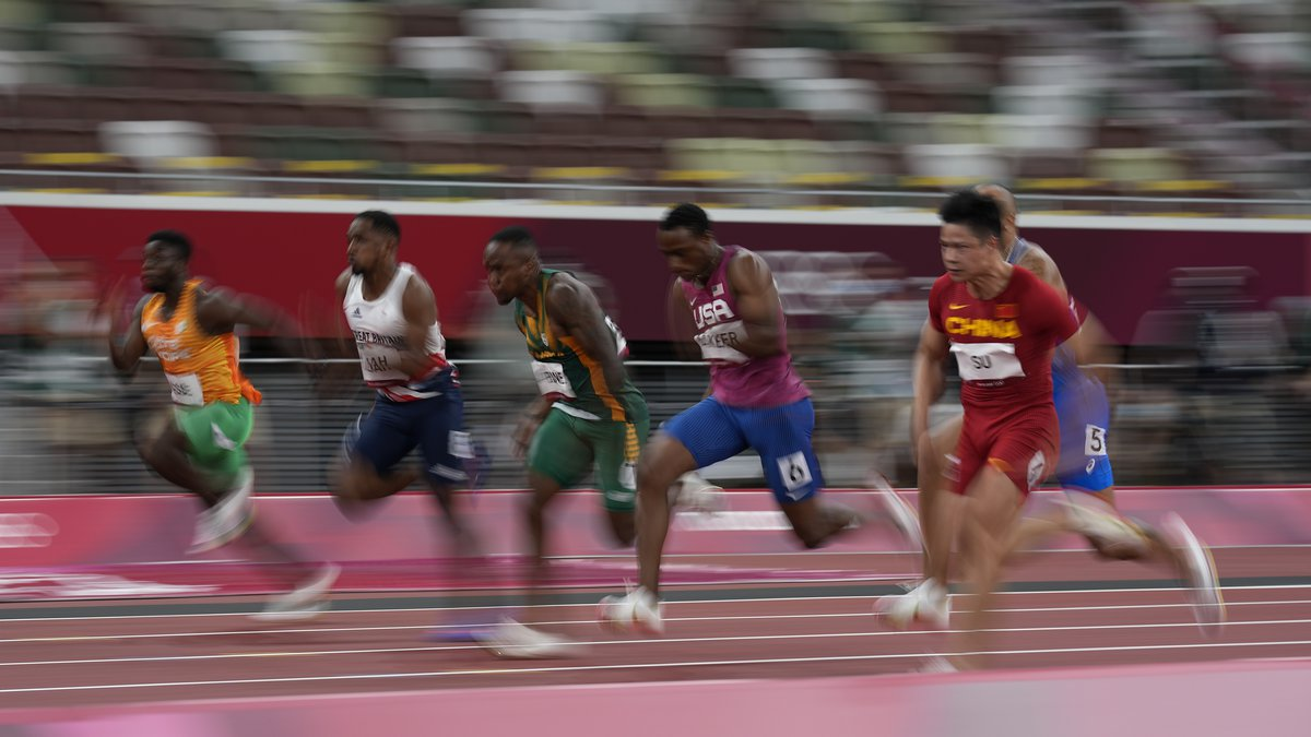 Ronnie Baker, center, of the United States, runs in a semifinal of the men's 100-meters at the...